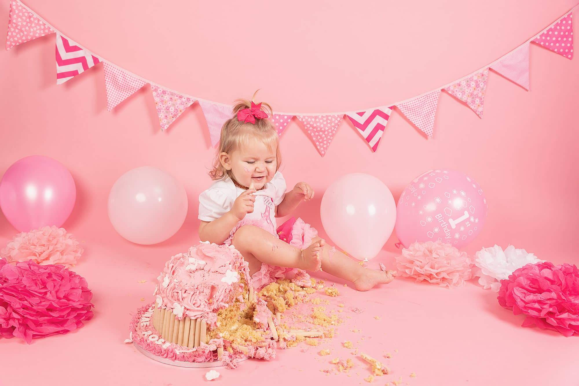 Cake smash photogapher Crawley. Pink backdrop with pink and white bunting. Little girl in tutu and white top with balloons and pom poms around her. Big giant cupcake with sponge sprinkled around her.