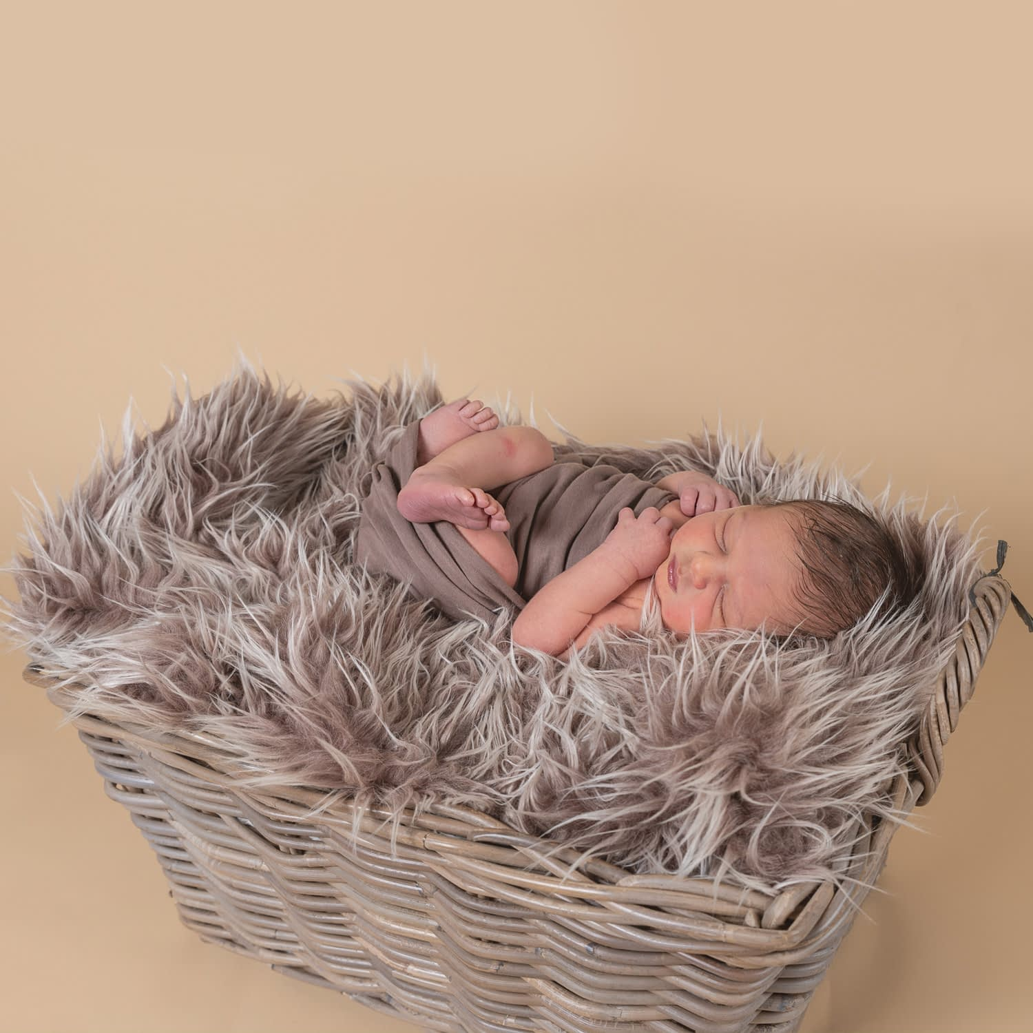 Newborn Photographer Crawley. Newborn baby boy laying on his back in a wicker basket on a brown fur blanket he is wrapped in a brown fabric with his arms and legs showing. Baby is sleeping and the background is a dark beige colour.